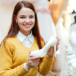 Bride chooses   shoes in wedding salon — Stock fotografie