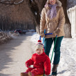 Mother with toddler on sled  in winter — Stock Photo