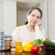 Weariness mature woman at  kitchen — Stock Photo