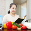 Woman cooking with cookbook in kitchen at home — ストック写真