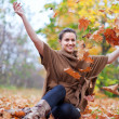 Happy girl throws maple - Stock Photo
