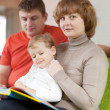 Parents with child looks book — Stockfoto #24185107
