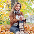 Woman sits in autumn park - Stock Photo