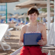 Woman using laptop at resort beach — Stock Photo