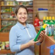 Mature womchooses fertilizers at store — Stock Photo #24185501