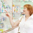 Woman chooses drugs at the pharmacy — Zdjęcie stockowe