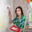 Girl paints wall with roller — Stock Photo #24185551
