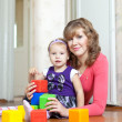 Mother and baby plays with toys at home — Stock Photo