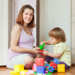 Pregnant mother plays with child - Stock Photo