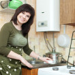 Woman cleans the kitchen sink - Stock Photo