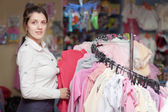 Woman chooses clothes at store — Stock Photo