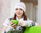 Girl warms with cup of tea at house — Stock Photo