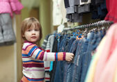 Child chooses jeans at shop — Stock Photo