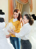 Saleswoman helps bride chooses bridal gown — Stock Photo