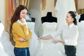 Saleswoman helps girl chooses white bridal gown — Stock Photo