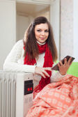 Woman reads e-reader near warm radiator — Stock Photo