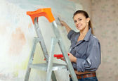 Woman paints wall with brush — Stock Photo