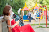 Woman reads e-book against playground area — Stock Photo