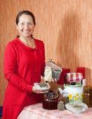 Mature woman brews herbs — Stock Photo