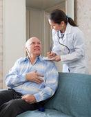 Vänlig läkare frågar mogen man känns — Stockfoto