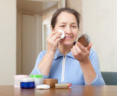 Mature woman cleans the make-up — Stockfoto