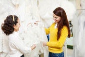 Consultant helps bride chooses bridal clothes at shop — Stock Photo