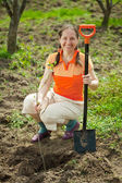 Mature woman planting tree — Stockfoto