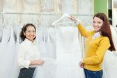 Assistente aiuta la sposa a scegliere l'abito da sposa — Foto Stock