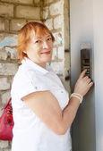 Woman pushing button of intercom — Stock Photo