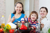 Mature woman and adult daughter with girl cook lunch — Stock Photo
