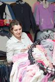 Kvinnliga köpare väljer vit blus — Stockfoto