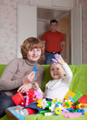 Happy mother and child plays with toys — Stock Photo