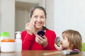 Grandmother with gitl puts facepowder — Stock Photo