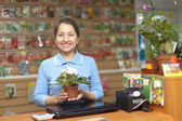 Female saleswoman at store for gardener — Stock Photo