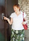 Mature woman uses intercom — Stock Photo