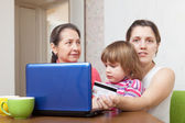 Two women and child shopping online — Stock Photo