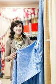 Mujer elige cortinas — Foto de Stock