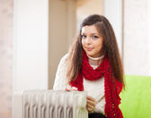 Long-haired woman near oil heater — Стоковое фото
