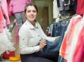 Woman chooses blue jeans at shop — Stockfoto
