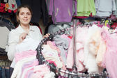 Woman chooses white blouse at shop — Stock Photo
