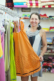 Woman chooses dress at shop — Foto de Stock