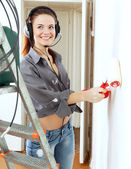 Girl in headphones paints wall — Stockfoto