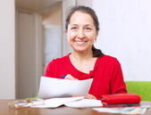 Joyful woman fills in payment documents — Stock Photo