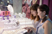 Women looking jewelry counter — Stock Photo