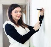 Kvinna vill driva spik i väggen — Stockfoto