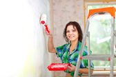 Happy woman paints wall — Stock Photo