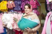 Woman with baby in sling at shop — Stock Photo