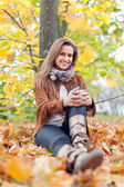 Woman sits in autumn park — Stock Photo