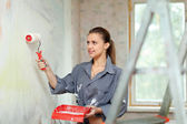 Woman paints wall with roller — Stockfoto