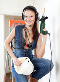 Sexy girl in headphones with drill and hardhat — Stock Photo